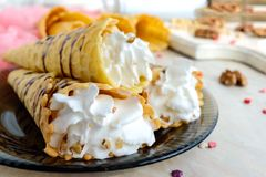 Delicious honeyed waffles, twisted into cones with cream, nuts, chocolate topping on the plate royalty free stock photo