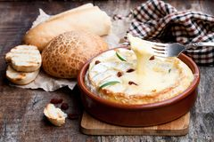 Delicious  hot baked camembert  with sultanas on wooden table. Delicious  hot baked camembert with sultanas on wooden table Royalty Free Stock Images