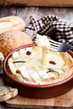 Delicious  hot baked  camembert with sultanas on wooden table. Delicious  hot baked camembert with sultanas on wooden table Royalty Free Stock Photo