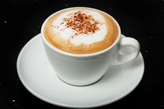 Delicious hot Cappuccino with cinnamon in a white cup. Royalty Free Stock Images