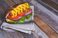 Delicious hot dog with toppings on dish cloth and wooden backgro Royalty Free Stock Images