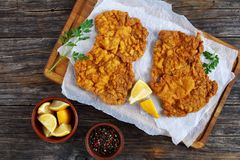 Delicious hot golden brown Wiener schnitzel. Delicious golden brown Wiener schnitzel prepared on classical authentic recipe served on cutting board with lemon stock photography