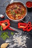 Hot beef goulas in a pot. Delicious hot hungarian goulash with beef meat, paprika, vegetables, in a pot. raw csipetke with dough on board, sweet pepper and soup royalty free stock photos