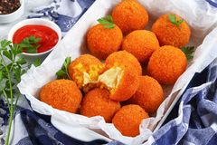 Delicious hot italian arancini in dish. Delicious hot italian arancini - saffron rice balls stuffed with cheese in baking dish on old wooden table with kitchen Royalty Free Stock Photos