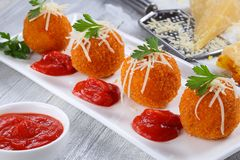 Delicious hot italian arancini on plate. Delicious hot italian arancini - saffron rice balls stuffed with melted cheese  topped with grated parmesan cheese and Royalty Free Stock Photos