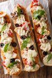 Delicious hot sandwich casserole pizza with chicken, cheese, tom. Atoes, olives and mushrooms close-up on the table. Vertical top view from above royalty free stock image