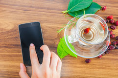 Delicious hot tea and mobile phone on table Stock Images
