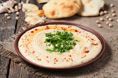 Delicious hummus creamy eastern traditional food. In bowl with pita on vintage wooden background Royalty Free Stock Image