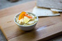 Delicious hummus on wooden board with the vegatables and pieces of bread. Royalty Free Stock Photography