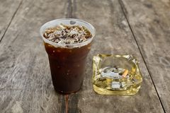 Delicious ice coffee americano  with cigarette on the old wooden Royalty Free Stock Images