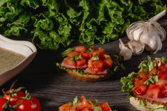 Delicious Italian antipasti bruschetta with chopped tomato, meat pate, sauce, cream cheese and salad leaves. Set of tasty. Appetizer sandwiches, close up royalty free stock photos