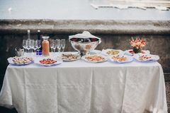 Delicious italian appetizers on table at wedding reception outdoors. Caviar, seafood, canapes, champagne and wine glasses on table. At wedding or christmas royalty free stock image