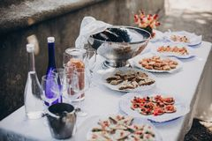 Delicious italian appetizers on table at wedding reception outdoors. Caviar, seafood, canapes, champagne and wine glasses on table. At wedding or christmas stock image