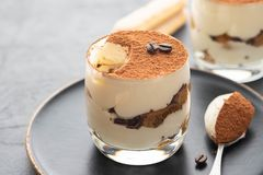 Delicious Italian dessert tiramisu, chocolate, cocoa and coffee beans on a black background. Copy space. royalty free stock photos