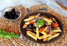 Delicious italian pasta penne with anchovies on a plate on a table. Royalty Free Stock Photos