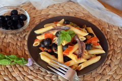 Delicious italian pasta penne with anchovies on a plate on a table. Royalty Free Stock Photo