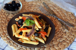 Delicious italian pasta penne with anchovies on a plate on a table. Royalty Free Stock Images
