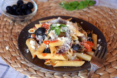 Delicious italian pasta penne with anchovies on a plate on a table. Stock Photos