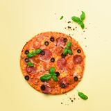 Delicious italian pizza, basil leaves, salt, pepper on yellow background with copyspace. Square crop. Top view. Banner. Delicious italian pizza, basil leaves Royalty Free Stock Image