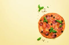 Delicious italian pizza, basil leaves, salt, pepper on yellow background with copyspace. Top view. Banner. Pattern for. Minimal style. Pop art design, creative Royalty Free Stock Photos