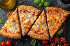 Delicious Italian pizza four cheeses with Basil, tomatoes and olive oil on a dark concrete table. Top view.  royalty free stock photos