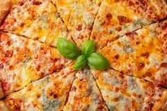 Delicious Italian pizza four cheeses with Basil, tomatoes and olive oil on a dark concrete table. Top view.  stock image