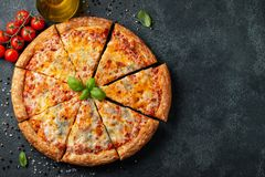 Delicious Italian pizza four cheeses with Basil, tomatoes and olive oil on a dark concrete table. Top view with copy space. Flat. Lay royalty free stock images