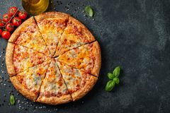 Delicious Italian pizza four cheeses with Basil, tomatoes and olive oil on a dark concrete table. Top view with copy space. Flat. Lay stock images