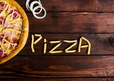 Delicious Italian pizza with French fries on a wooden table royalty free stock images