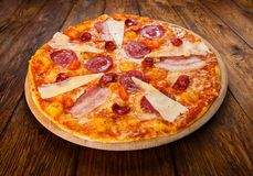 Delicious italian pizza with salami, bacon and parmesan Stock Image
