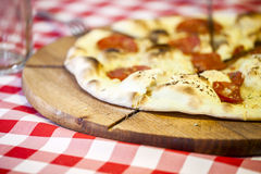 Delicious Italian pizza served on wooden board. Royalty Free Stock Image
