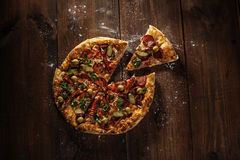 Delicious italian pizza with slice served on wooden table Stock Image