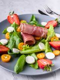 Delicious italian salad with greens, strawberries, bresaola, lumps and mozzarella. Tasty and healthy food. Close up royalty free stock photos