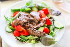 Delicious juicy barbequed steak. Grilled meat beef lamb garnished with tomatoes ,tomatoes and vegetables stock images
