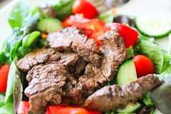 Delicious juicy barbequed steak. Grilled meat beef lamb garnished with tomatoes ,tomatoes and vegetables stock photos