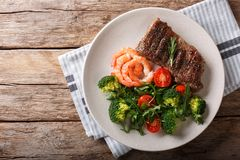 Delicious juicy barbequed steak and prawns with vegetable salad stock image