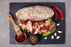 Delicious juicy giant BBQ rib sandwich. Close-up of delicious juicy giant BBQ rib sandwich of rye bread loaf with fresh green lettuce, shredded pork meat, and Royalty Free Stock Photo