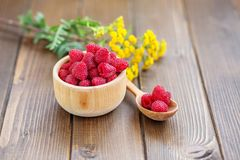 Delicious juicy raspberries in a wooden bowl. Top view. The conc. Ept is healthy food, diet, vegetarianism, vitamins Stock Photos
