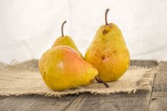 Yellow pear on a rustic background. Delicious, juicy, ripe, yellow pear on a rustic background on a wooden table and a white background Royalty Free Stock Photography