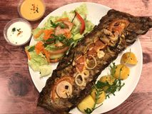Delicious, juicy spare ribs with fried potatoes, vegetables, salad and sauces. stock photo