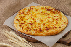 Delicious khachapuri with wheat ears on sacking Royalty Free Stock Image
