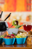 Delicious kiwi in a metal stick with assorted fresh fruits inside of bowls with red wine in a cup on wooden table.  Royalty Free Stock Images