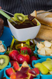 Delicious kiwi and a piece of bread in a metal stick covered with chocolate fondue inside of a white bowl with assorted. Fruits in bowls on wooden table Royalty Free Stock Photos