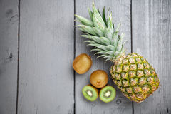 Delicious kiwi and pineapple fruit on grey wooden background. Delicious and healthy kiwi and pineapple fruit on grey wooden background Royalty Free Stock Photos