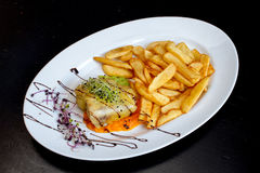 Delicious Krombacher Sirloin with Fried Potatoes and Onion Sprouts. On a white plate food photography Royalty Free Stock Images