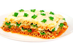 Delicious lasagna slice on a plate. Isolated on white background Royalty Free Stock Image
