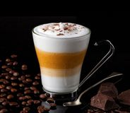 Latte macchiato with coffee beans an chocolate chunks. Delicious latte macchiato coffee in a glass cup surrounded by coffee beans and chocolate chunks Stock Images