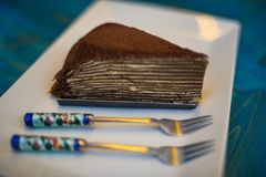 Delicious layered cake served on plate with fork stock photography