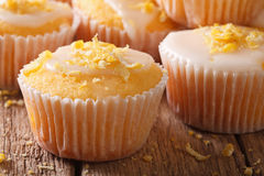 Delicious lemon muffins with icing and zest macro. Horizontal Royalty Free Stock Photography