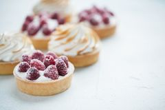 Delicious lemon and raspberry tartlets with meringue on a white vintage plate. Sweet treat on a light blue background. copy space.  Royalty Free Stock Images